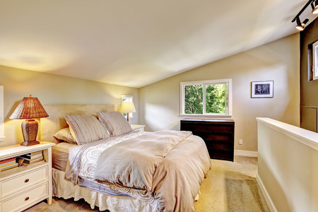 vaulted: Bright light tones bedroom with vaulted ceiling and beautiful bed. Stock Photo