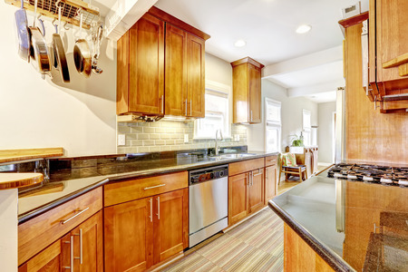 kitchen cabinets: Bright brown kitchen cabinets with black granite tops. Kitchen room with tile back splash trim, hardwood floor and stripped rug