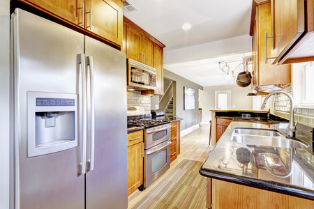 black appliances: Bright brown kitchen cabinets with black granite tops and steel appliances. Kitchen room with tile back splash trim, hardwood floor and stripped rug.