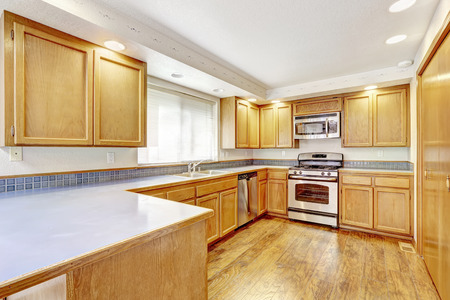 counter top: Spacious kitchen area in empty house. Light tones wooden cabinet with steel appliances and white counter top Stock Photo