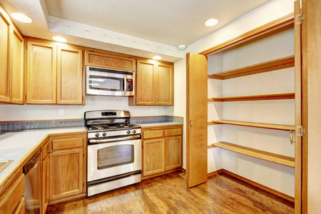 Kitchen area in empty house. Light tones wooden cabinet with steel appliances and white counter top. Storage room with shelves photo