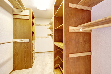 Empty walk-in closet with wooden cabinets with drawers
