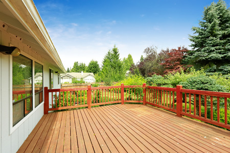 One story house with wooden walkout deck overlooking backyard garden