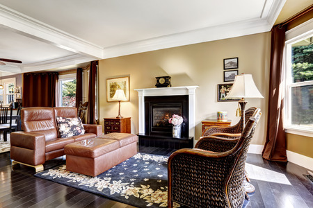 Luxury home interior in brown tones with fireplace, antique chairs, leather couch and ottoman photo