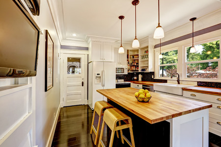 kitchen island: White kitchen cabinet with white appliances. Kitchen island with wooden counter top and stools