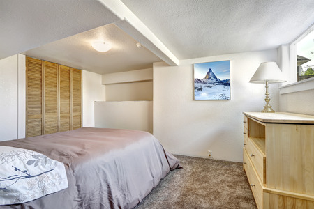 Cozy bedroom with low ceiling and soft brown carpet floor photo