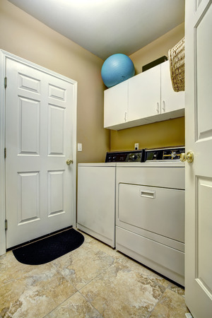 laundry room: Simple laundry room interior with white cabinets and appliances.
