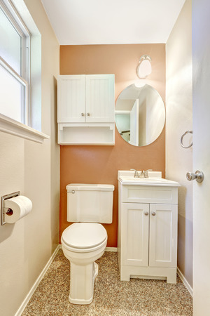 bathroom mirror: White and orange small bathroom with white cabinet and mirror