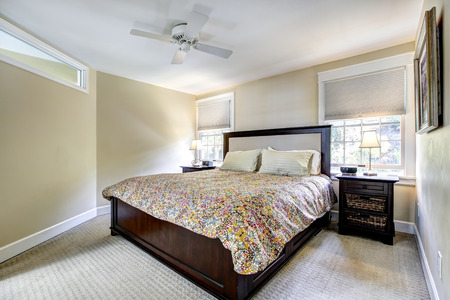 nightstands: Light ivory bedroom interior with dark brown bed and nightstands