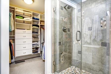 closet door: Modern bathroom interior with glass door shower and walk-in closet