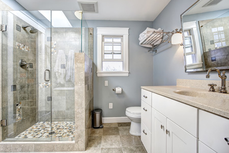 Light blue modern bathroom interior with glass door shower and white cabinet with  mirror photo