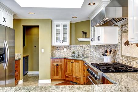 brown granite: Modern house interior. White and brown kitchen room with shiny granite tops and mosaic backsplash trim