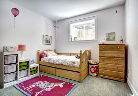 Cozy kids room with rustic bed and dresser. Cheerful red rug on carpet floor Stok Fotoğraf