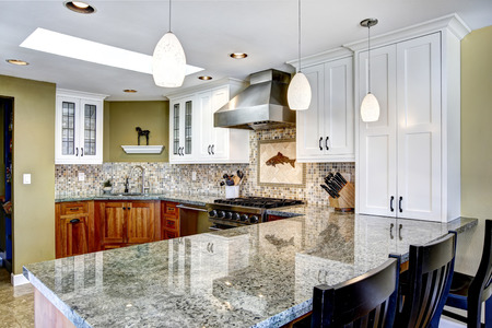 Modern house interior. White and brown kitchen room with shiny granite tops and mosaic backsplash trim photo