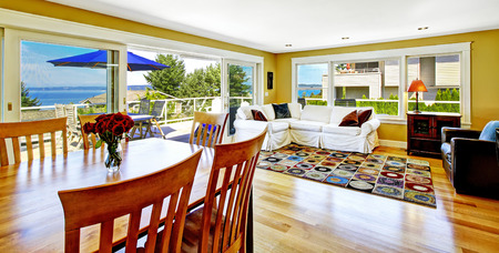bay area: Bright living room with white sofa and dining area. Spacious walkout deck overlooking scenic bay view. Tacoma real estate, WA