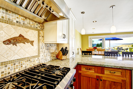 Modern house interior. White and brown kitchen room with shiny granite tops and mosaic backsplash trim