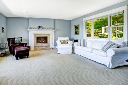 Light blue living room with white sofa, armchair and leather chair and cozy fireplace