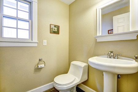 Light Yellow Bathroom Wtih White Toilet, Washbasin Stand And Mirror Stock  Photo   31616159