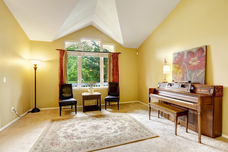Bright yellow room with vaulted ceiling. Carved wood piano, two leather chairs and small table photo