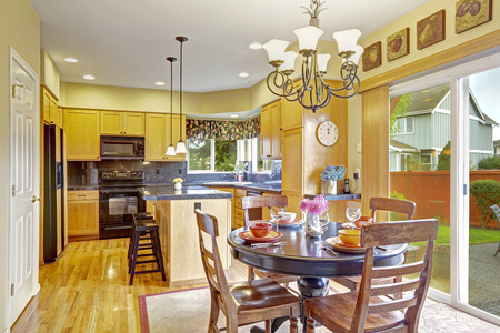 designer chair: Bright dining area in kitchen room with exit to backyard patio Stock Photo