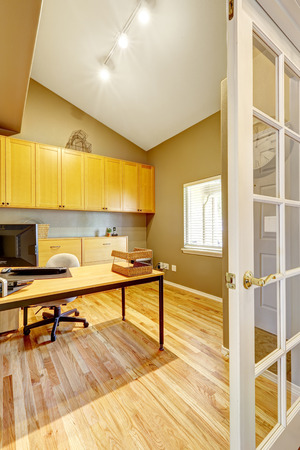 Practical office room design. White vaulted ceiling, beige wall and new hardwood floor. photo