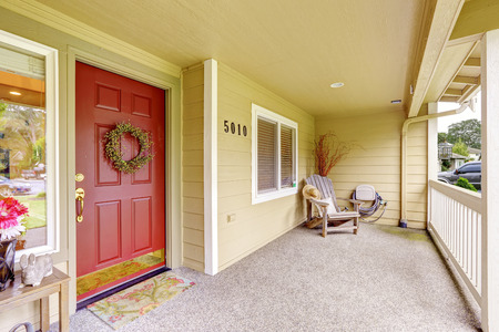 Spacious entrance porch with red door and wooden chair photo