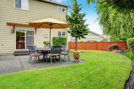 Patio area with table set and umbrella. Backyard landscape Stock Photo