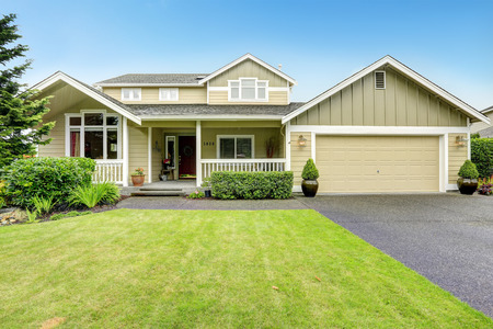 House exterior. Spacious walkout deck with railings. Garage with driveway Stok Fotoğraf
