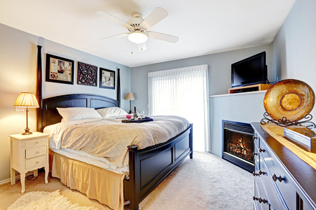 Light blue master bedroom with queen size bed, dresser. Room has fireplace and TV photo