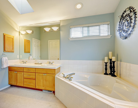 corner tub: Refreshing bathroom interior with vanity cabinet with mirror and corner bath tub Stock Photo