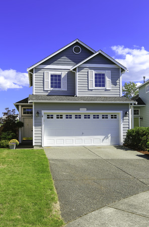 garage on house: Two story house with small entrance porch and garage with driveway