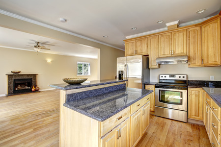 kitchen island: Kitchen area in empty house. Kitchen island with granite top and empty living room with fireplace