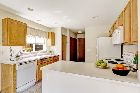 kitchen cabinets: Simple kitchen interior in bright white color with wooden cabinets