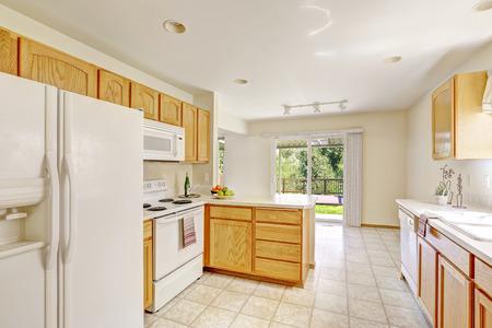 Interior de la cocina simple en color blanco brillante con armarios de  madera. Comedor vacío con cubierta de huelga
