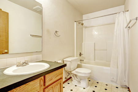 linoleum: Simple bathroom interior with linoleum floor, wooden cabinet with mirror and white bath tub with curtains