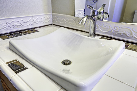 counter top: Bathroom with white sink with steel faucet. Tile counter top Stock Photo