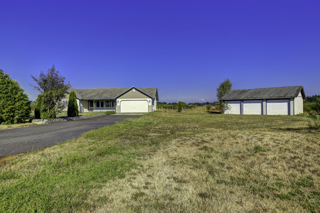 residential garage: Countryside house exterior with three car garage building and landscape. Washington real estate