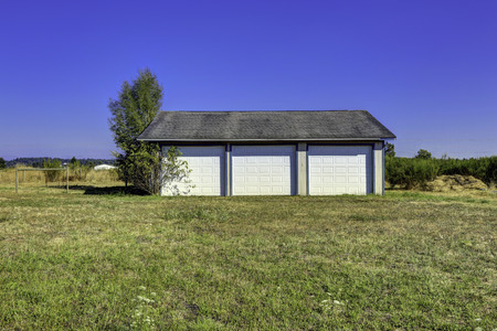 Three car garage with tile roof and white doors. Countryside landscape