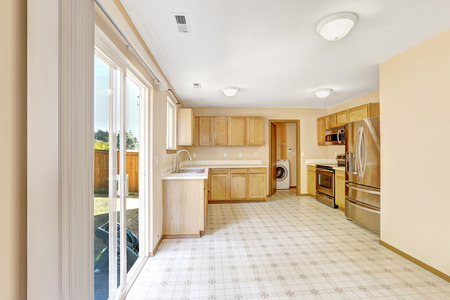 Bright kitchen room in countryside house. Room has laundry area and exit to backyard area