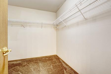 walk in closet: Empty walk-in  closet with brown carpet floor and shelves