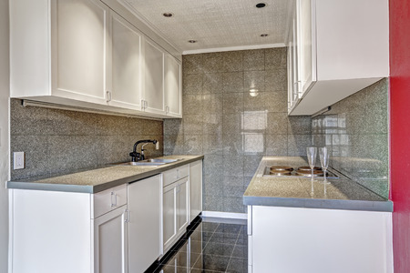 white trim: White kitchen cabinets with grey tile wall trim and tile floor