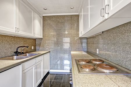 kitchen tile: White kitchen cabinets with grey tile wall trim and tile floor