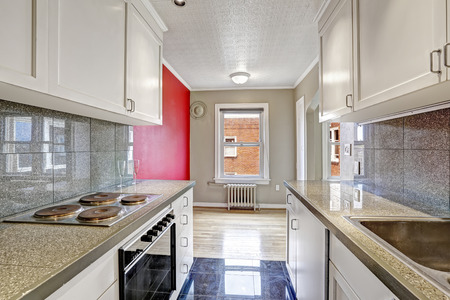 kitchen cabinets: White kitchen cabinets with grey tile wall trim and tile floor. Empty dining area with grey and red walls Stock Photo