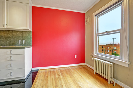 Empty apartment. Dining area with bright red wall, hardwood floor and window photo