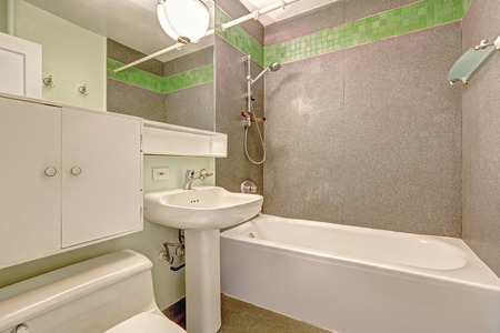 white trim: White bahtroom interior with grey wall and green tile trim