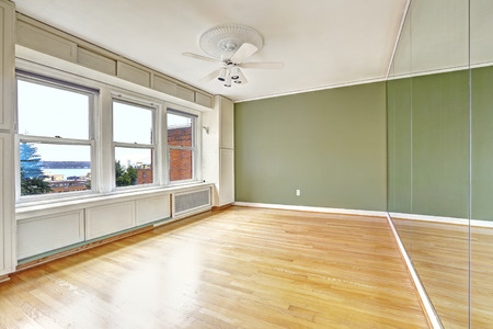 mirror on wall: Empty apartment interior in old residential building with bay view. Downtown, Seattle. Bedroom with green wall and large mirror. Old window system Stock Photo