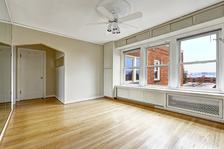 Empty apartment interior in old residential building in Downtown, Seattle. Bedroom with hardwood floor and old window system photo