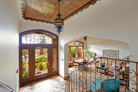 foyer: Foyer in old residential building in Downtown, Seattle. Mosaic tile floor, decorated ceiling and wooden entance door together with wrough iron railings merge a visitor into historic atmosphere