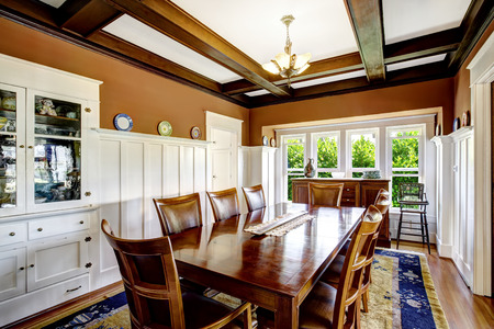 white trim: Large dining table set in brown room with white trim and coffered ceiling