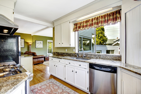 granite kitchen: Kitchen area with white cabinets, granite tops and steel dishwasher